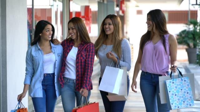 話していると、買い物袋を運ぶ店隣を歩いていたショッピング モールでラテン アメリカの友人の美しいグループ - 買い物袋点の映像素材/bロール