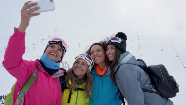 vídeos de stock e filmes b-roll de beautiful group of multi ethnic female friends taking a selfie hiking the mountain during winter - snowboard