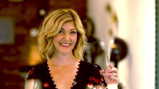 vídeos de stock e filmes b-roll de beautiful hairdresser holds scissors welcoming new clients - trabalhadora de colarinho branco