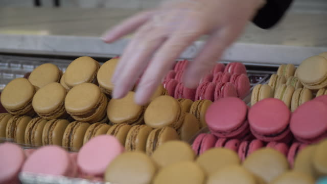 beautiful hand pick up  sweet macarons - macaroon stock videos and b-roll footage