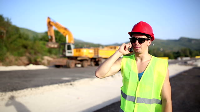 Beautiful handsome construction worker on the phone