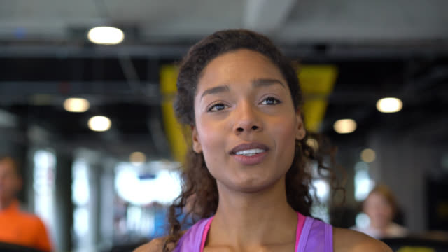 stockvideo's en b-roll-footage met mooie gelukkig zwarte vrouw op de sportschool draait op loopband - loopband fitnessapparaat