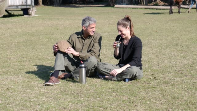 beautiful happy couple at a farm taking a break drinking mate while talking - yerba mate stock videos & royalty-free footage