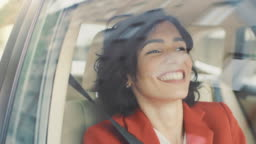 Beautiful Happy Woman Rides on a Passenger Seat of a Car, She's Happy and Dances. Big City View Reflects in the Window. Camera Mounted outside Moving Car.