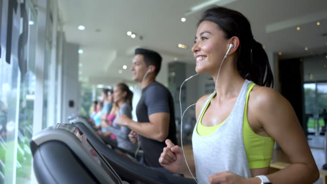 beautiful happy woman running on the treadmill smiling - males stock videos & royalty-free footage