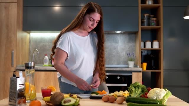 Schöne gesunde, gesunde Frau bereitet einen veganen Teller vor