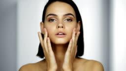 Beautiful healthy woman touching smooth skin
