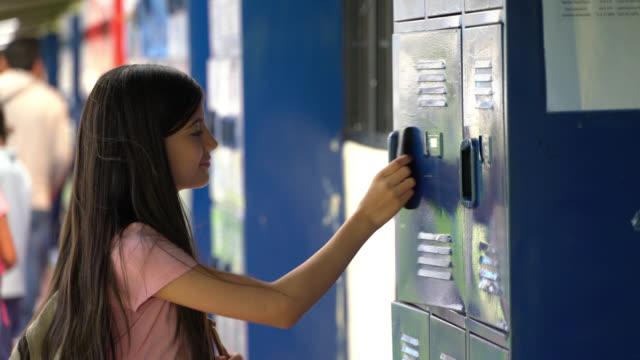 美しい高校生が学校でノートをつかむためにロッカーに歩いて - ロッカー点の映像素材/bロール