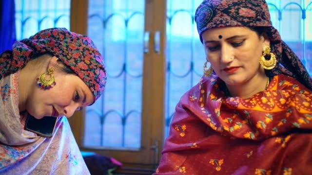 vidéos et rushes de belle femme himachali avec soeur épluche des pois et parle sur un smartphone. - châle