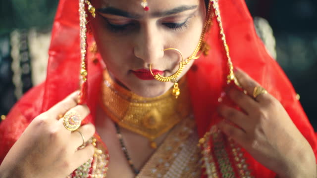 beautiful hindu bride in traditional dress looks at the camera. - gold dress stock videos & royalty-free footage