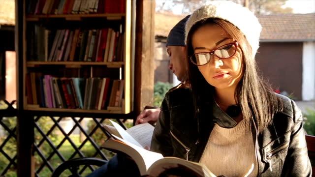 vidéos et rushes de couple de hipster belle lecture d'un livre - rangement