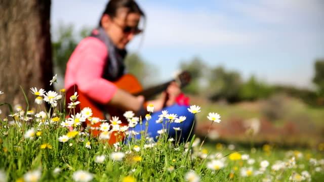 Schöne hipster Mädchen spielt Gitarre im Feld