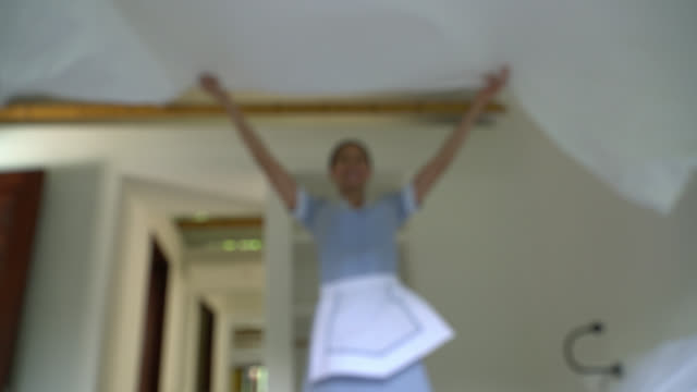 beautiful hotel maid making the bed at a hotel - bedclothes stock videos & royalty-free footage