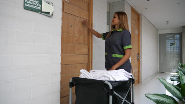 beautiful house keeper knocking on door to put towels in the room - lavori di casa video stock e b–roll