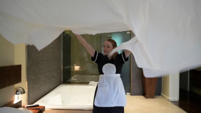 beautiful house keeper making the bed at the hotel putting the bed sheet on the bed smiling - lavori di casa video stock e b–roll