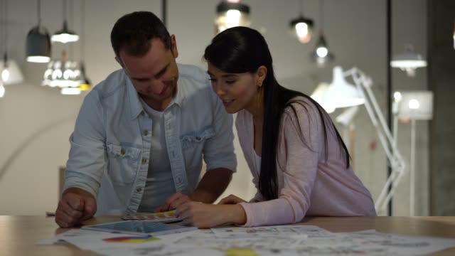 Schönes Interieur-Designer und Kunden in einem Geschäft Blick auf Tablet und ein Farbfeld beim sprechen