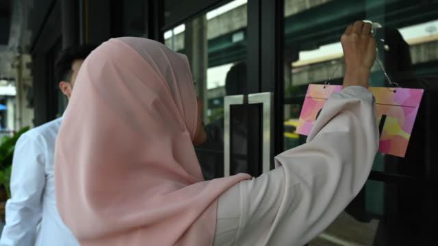 vidéos et rushes de beautiful islamic woman and asian man happily putting up 'open' sign - vêtement religieux