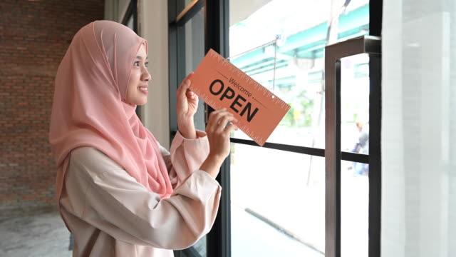 "vidéos et rushes de beautiful islamic woman cheerfully putting up ""open"" sign - vêtement religieux"