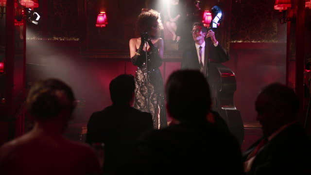 Beautiful Jazz Singer Performs In front of crowd backed up by bass player.