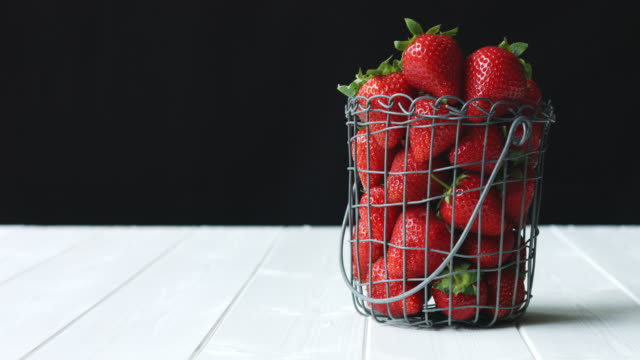 beautiful, juicy seasonal strawberries on a white wooden surface against a black background - juicy stock videos & royalty-free footage