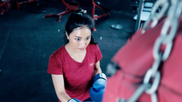 Beautiful kickboxing woman training with the punching bag in a gym, slow motion