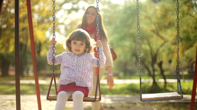stockvideo's en b-roll-footage met beautiful kid and mother play outdor on swing - speeltuin