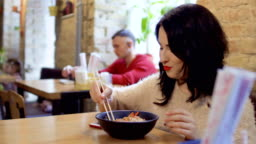 Beautiful korean with red lips enjoys rice noodles in Korean restaurant