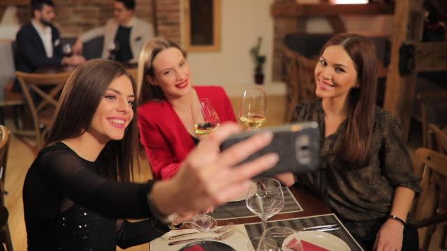 Beautiful ladies taking a selfie in restaurant