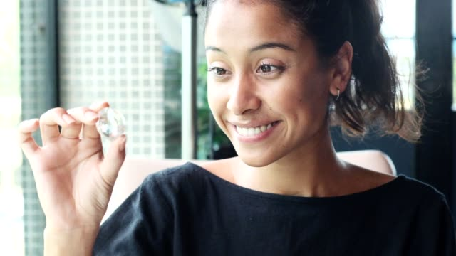 beautiful lady half thai and half americanlooking to the crystal received as a gift. slow motion - quartz stock videos & royalty-free footage