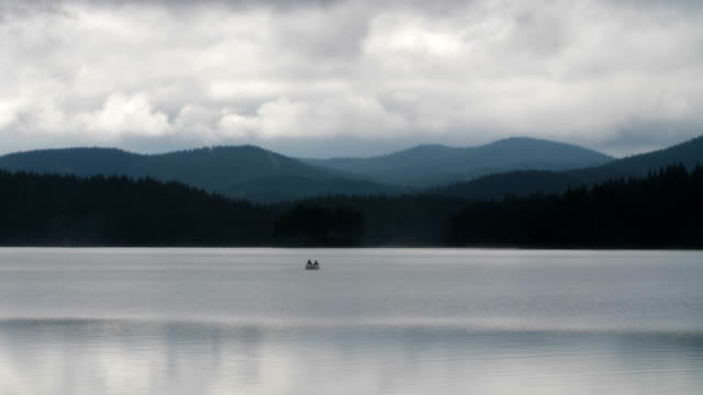 beautiful landscape of two people in a boat far away on the horizon rowing in a boat around a mountain lake - rowing boat stock videos & royalty-free footage