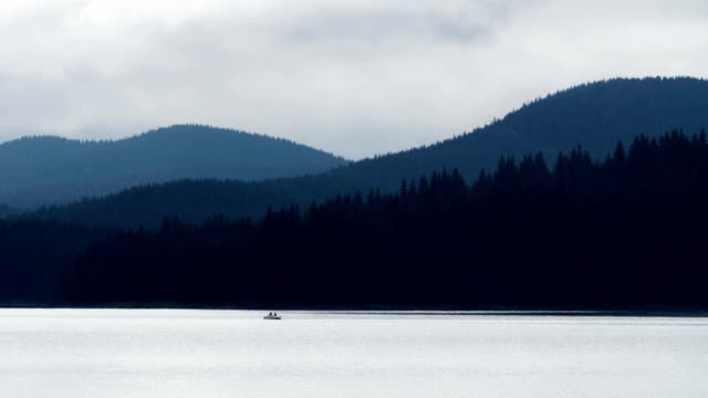 Beautiful landscape of two people in a boat far away on the horizon rowing in a boat around a mountain lake