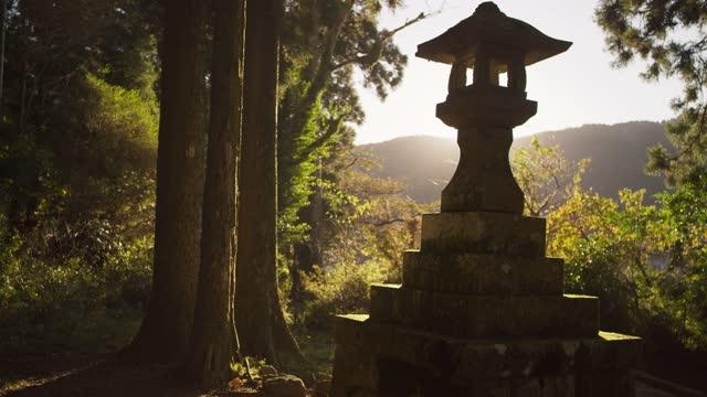 beautiful lantern statue next to lake in japanese forest - schrein stock-videos und b-roll-filmmaterial