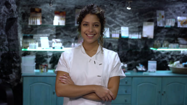 beautiful latin american beautician working at a spa looking at camera with arms crossed smilin - massage stock videos & royalty-free footage