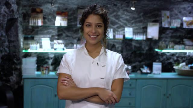 schöne lateinamerikanische kosmetikerin arbeiten in einem spa blick auf die kamera mit dener armen gekreuzt smilin - spa treatment stock-videos und b-roll-filmmaterial