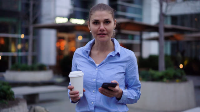 beautiful latin american businesswoman enjoying a takeout coffee and chatting on phone while looking at camera smiling - fare una pausa video stock e b–roll