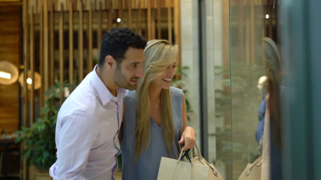 beautiful latin american couple at the mall looking at the store window pointing while talking - shopping centre stock videos & royalty-free footage