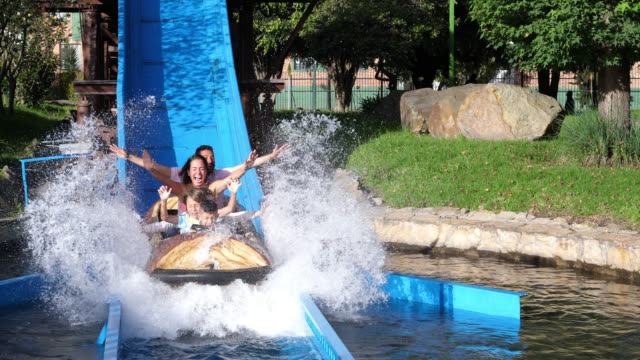 beautiful latin american family on a log ride at an amusement park having fun with arms up - water slide stock videos & royalty-free footage