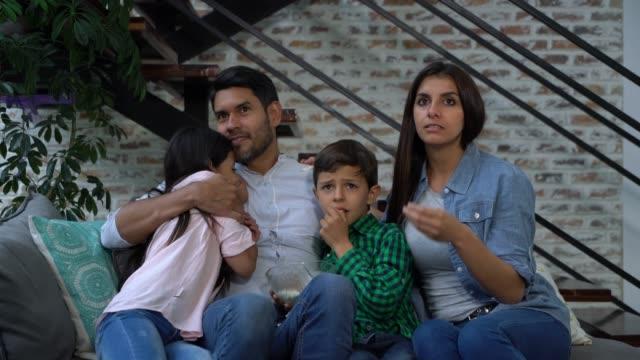 schöne lateinamerikanische familie zu sehen, einen beängstigenden film sieht versteinert - horror movie stock-videos und b-roll-filmmaterial