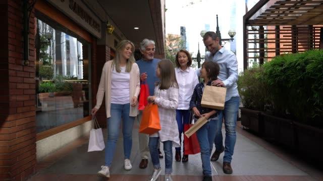 ショッピングモールで祖父母と美しいラテンアメリカの家族と楽しい時を過す - 買い物袋点の映像素材/bロール