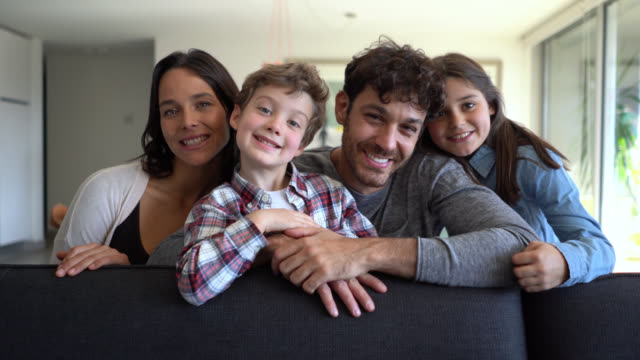 Beautiful latin american family with two children smiling at camera very happy while sitting on couch