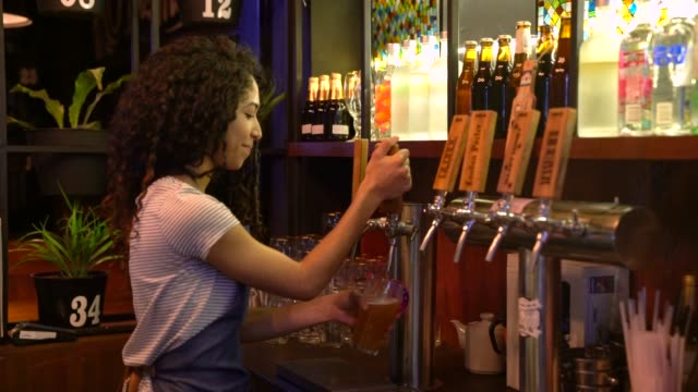 beautiful latin american female bar tender serving beer and then facing camera smiling - bartender stock videos & royalty-free footage