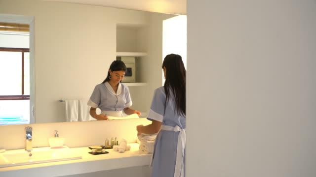 Vackra latinamerikanska piga vika handdukar i badrummet