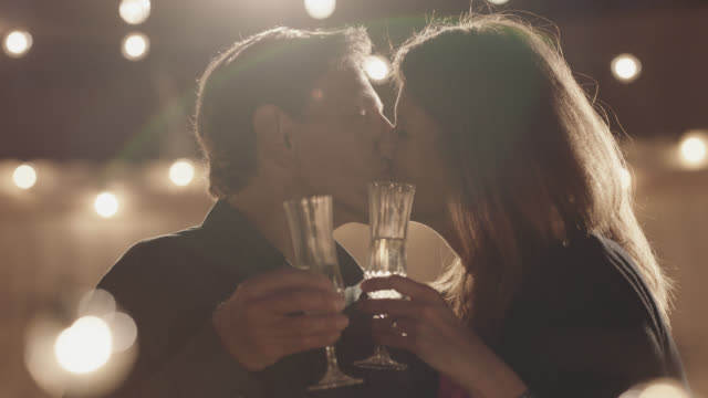 slo mo. cu. beautiful latin american mature couple toast champagne flutes and kiss - music stock videos & royalty-free footage