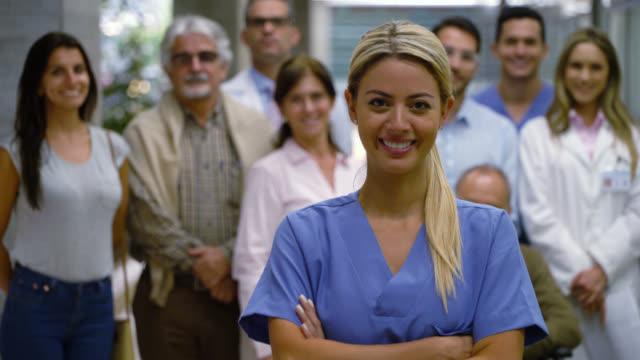 vídeos de stock, filmes e b-roll de a enfermeira latino-americana bonita enfrenta a câmera com os braços cruzados quando os pacientes e os doutores estiverem no fundo que sorriem - braços cruzados