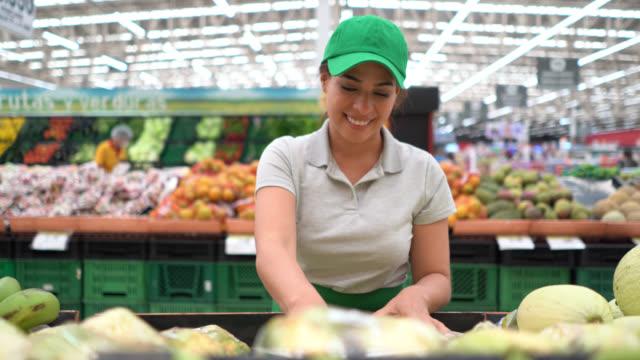スーパーで果物や野菜のディスプレイを手配する美しいラテンアメリカの販売女性 - 店頭点の映像素材/bロール