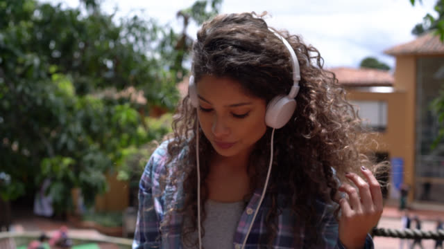 Beautiful latin american student putting on her headphones to listen music while at the college campus
