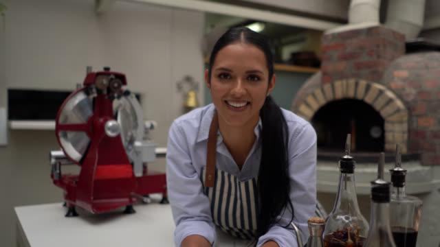 美しいラテンアメリカのウェイトレスは、レストランで働き、キッチンカウンターに身を乗り出して笑顔のカメラを見て - 整える点の映像素材/bロール