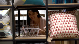 Beautiful latin american woman at a store looking at a basket on shelf very happy
