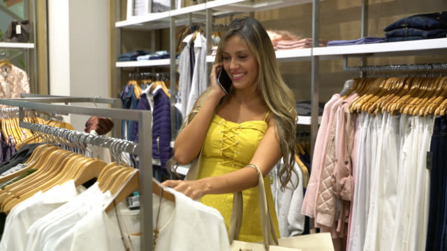 beautiful latin american woman at a women's clothing store shopping while talking on her phone - all shirts stock videos and b-roll footage