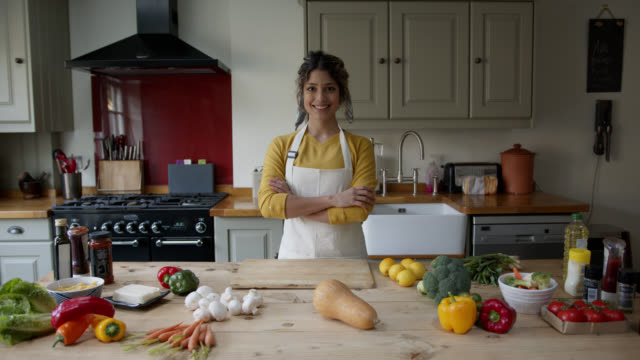 vídeos de stock e filmes b-roll de beautiful latin american woman at home with fresh delicious vegetables on counter ready to prepare a vegan meal smiling at camera - latin american and hispanic ethnicity
